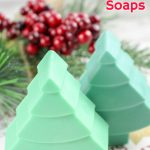 three christmas tree soaps in different shades of green next to pine needles and holly berries