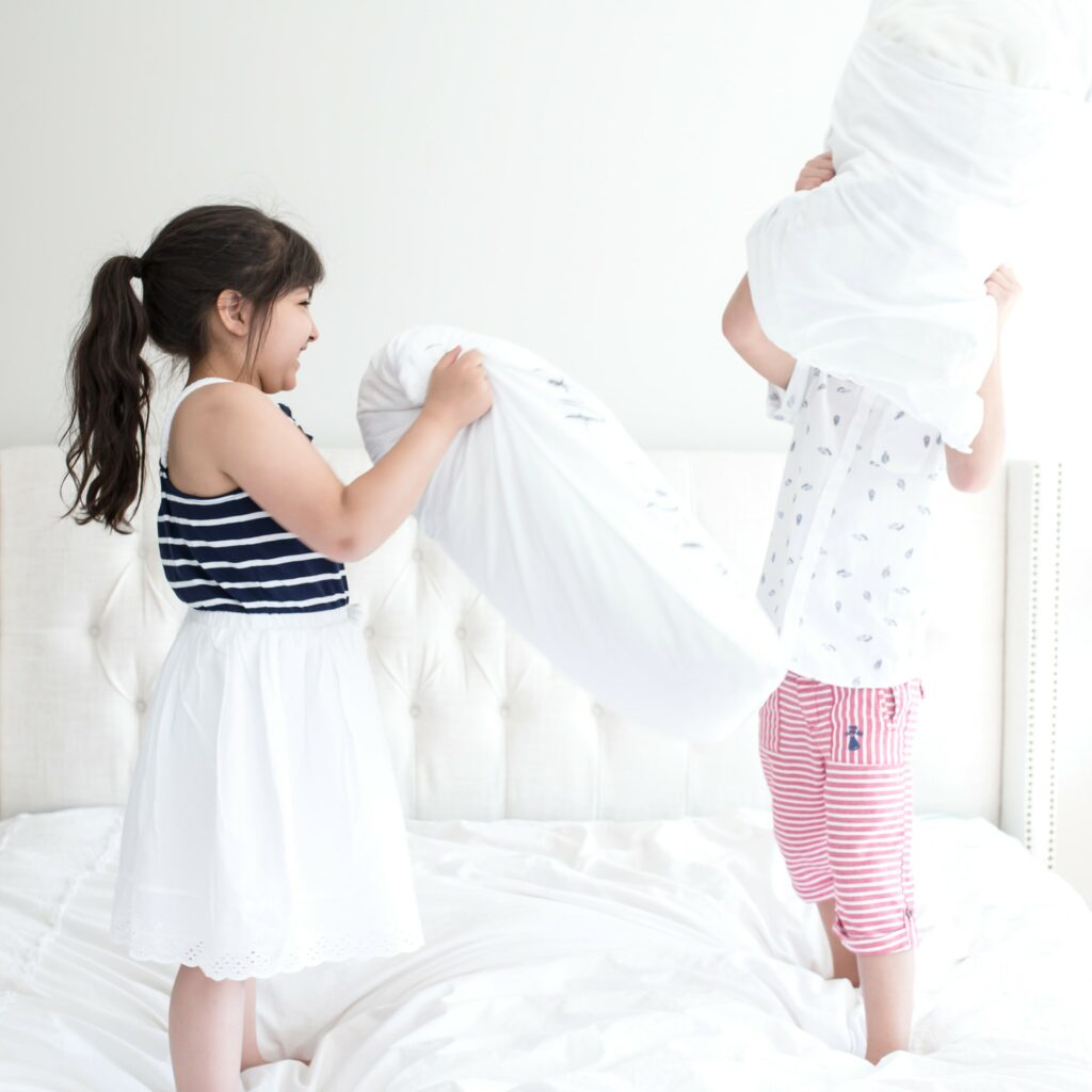 two children jumping on white comforter on bed throwing pillows