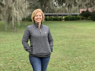 woman wearing tentree pullover and jeans standing on green grass