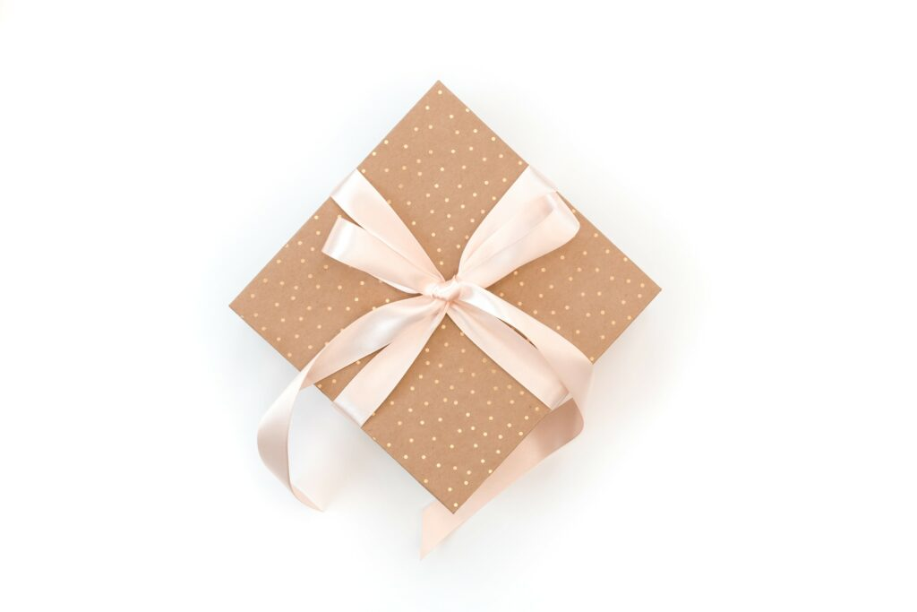 gift wrapped in brown and gold polka dot wrapping paper with pink bow against white background
