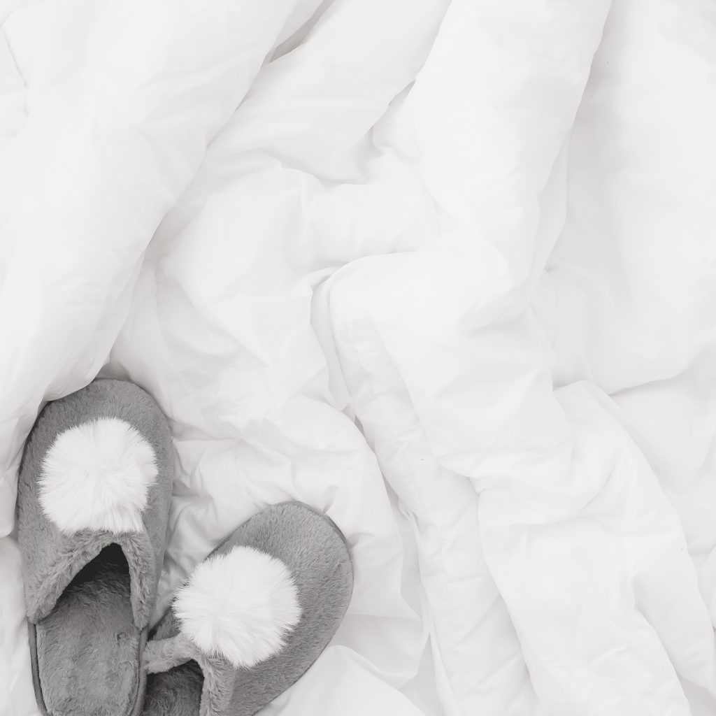 white comforter bunched up with fuzzy grey slippers on bed