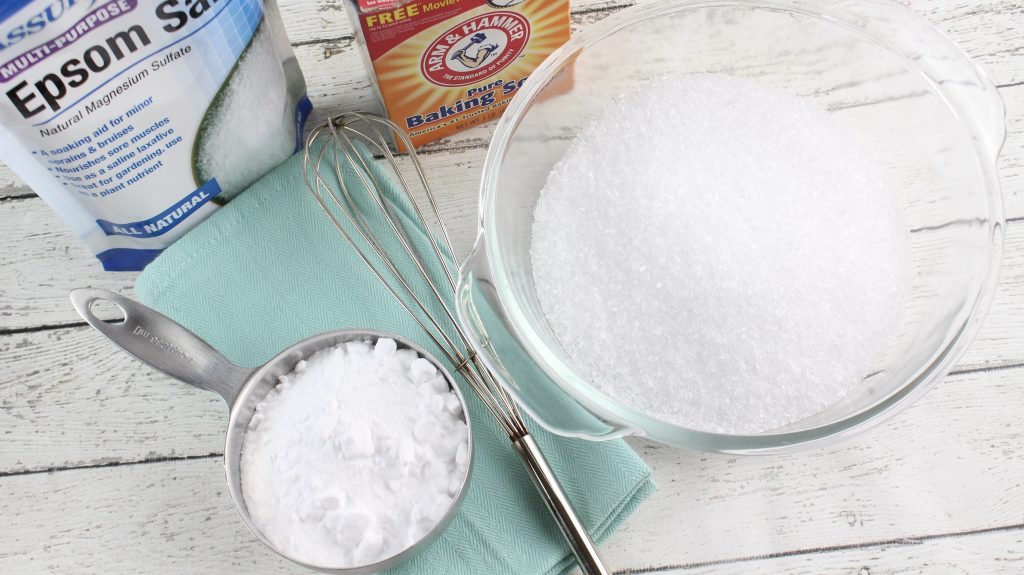 Baking soda box next to glass bowl of nasal decongestant bath salts on white wooden table