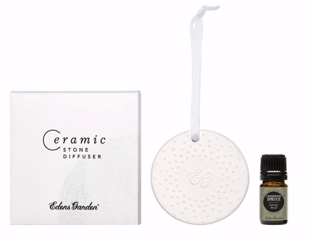 ceramic essential oil diffuser on a string and essential oils bottle against white background