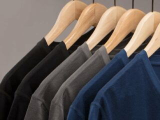 black grey and blue wool shirts hanging on wooden hangers against gray background