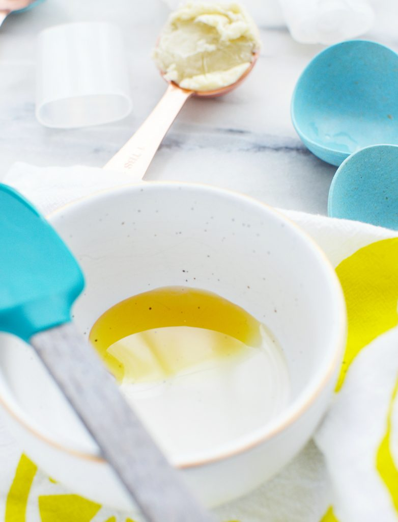 liquid oil in white ceramic bowl with blue spatula against white marble table