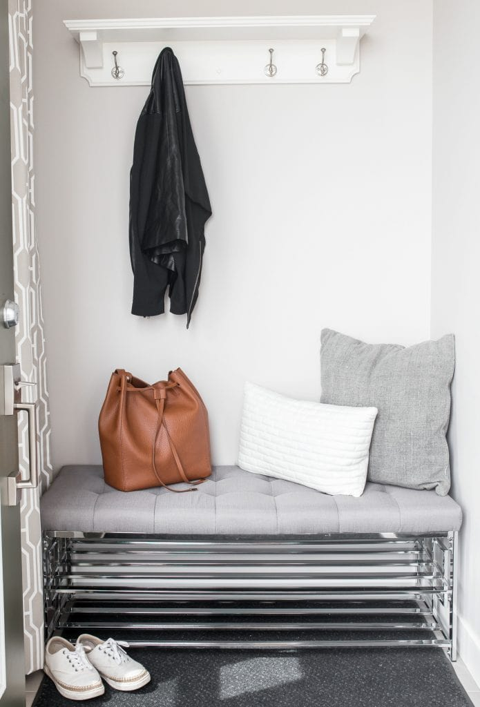 wire bench in entry way with grey cushions brown leather purse and coat hanging on hooks
