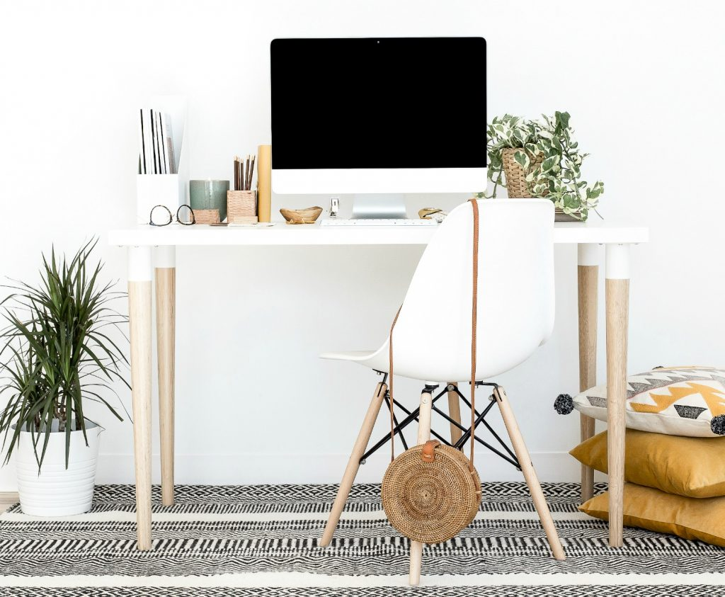 indoor plants on office desk with computer and desk chair against white background