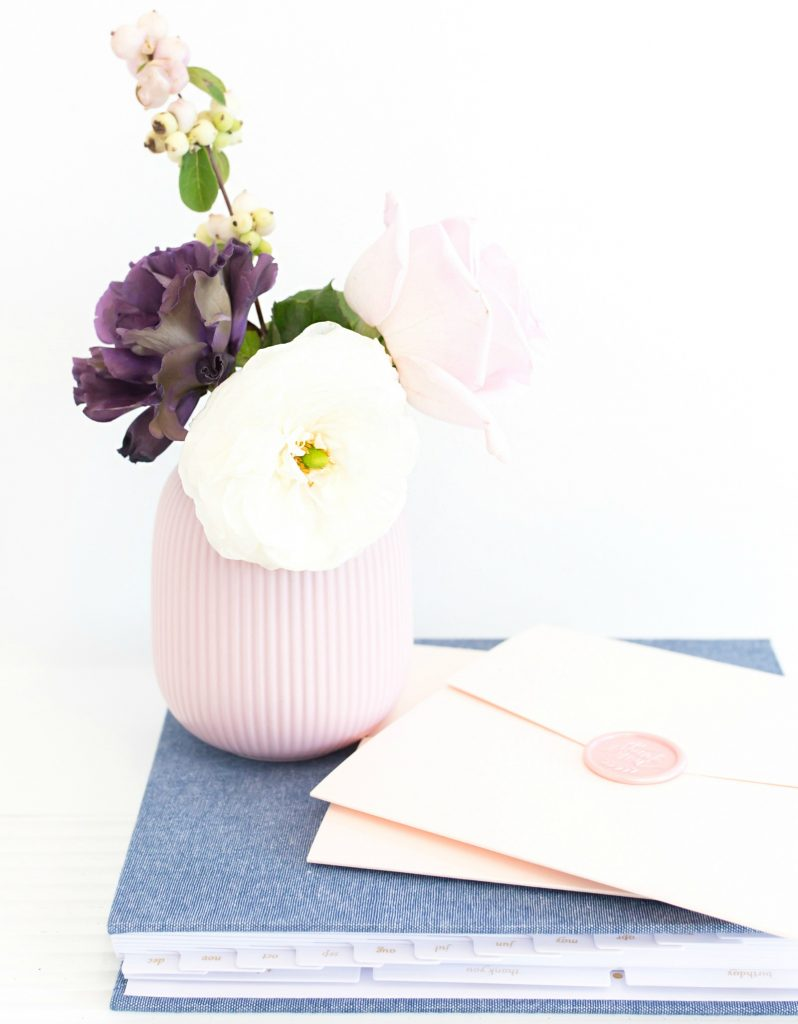 pink envelope on blue journal next to purple vase filled with fresh flowers