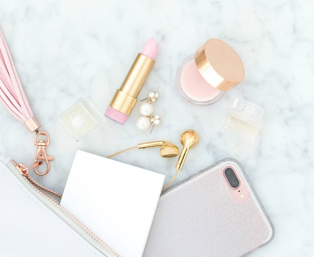 emptied purse with lipstick makeup phone earrings and ear buds with pink leather tassel against white marble background
