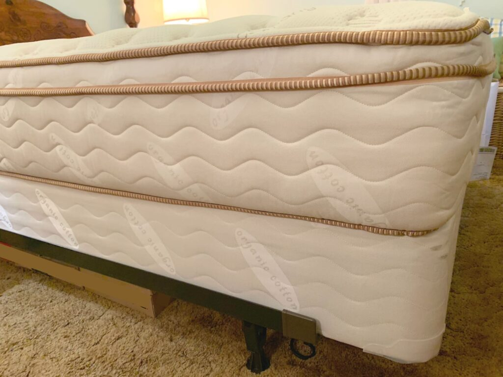 Saatva mattress on box springs on bed frame on carpet in bedroom