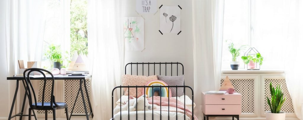 teenagers bedroom with bright airy windows, pink accents lots of green plants and black metal furniture