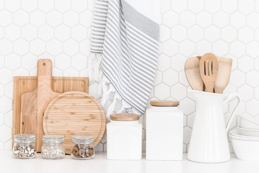 wooden cutting boards white storage containers and glass mason jars against white backsplash in kitchen