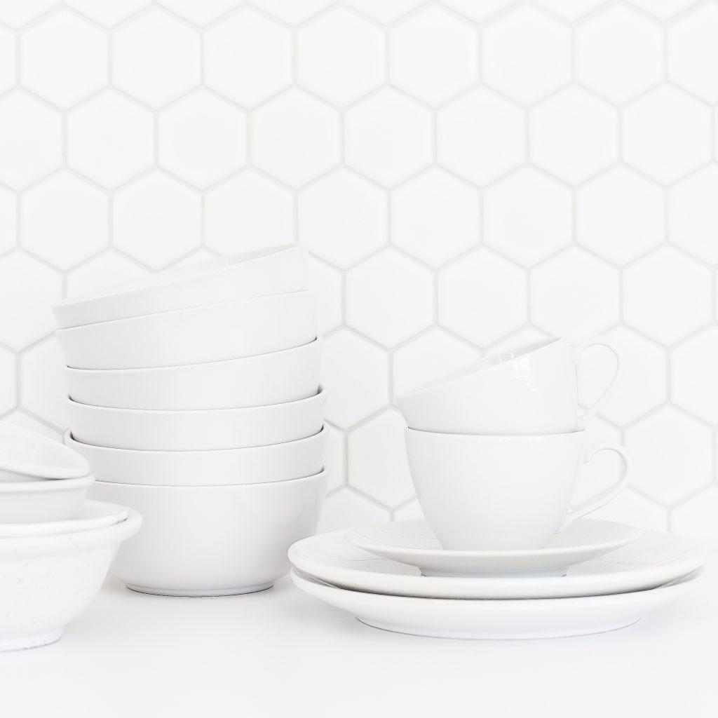 minimalism white dishes mugs bowls against white backsplash uncluttered