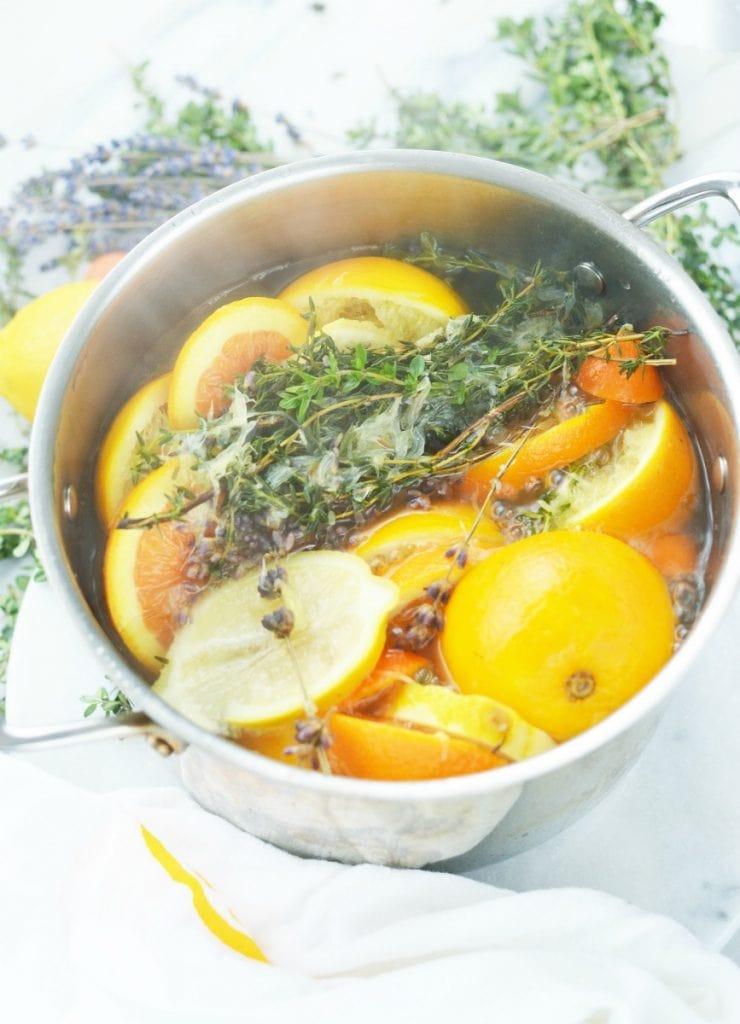 orange lemon lavender thyme herb in boiling water in stainless steel simmer pot on white marble stove top potpourri