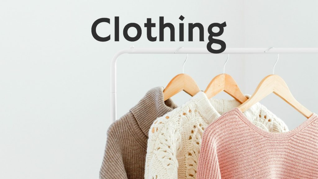 sweaters hanging on hangers on clothing rack against white wall