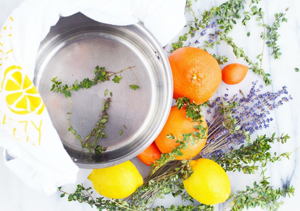 orange lemon lavender thyme herb on marble slab with stainless steel simmer pot and white towel for stove top potpourri