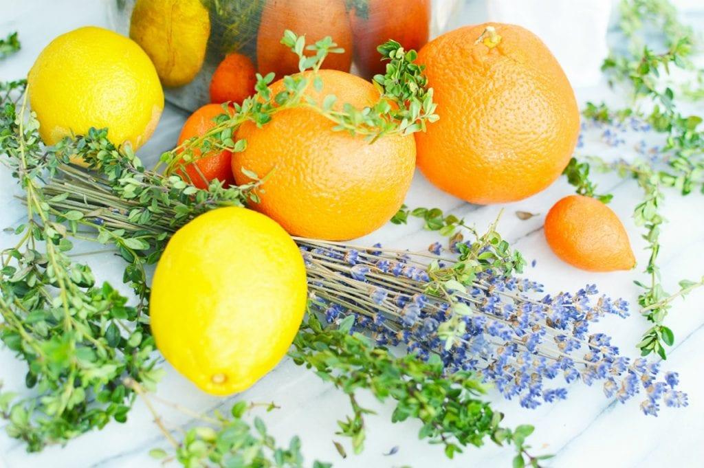lemons oranges thyme herbs lavender flowers on white marble slab simmering stovetop popurri