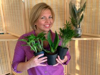 Woman wearing purple shirt against wicker background showing houseplant pots from best place to buy indoor plants online