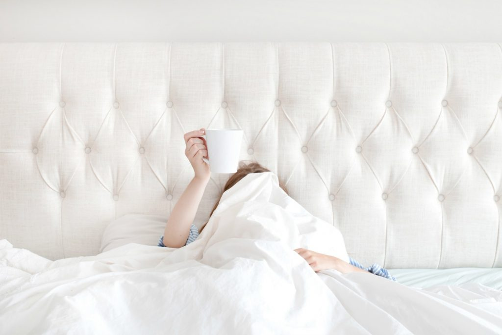 woman hiding under white sheets in bed holding up coffee cup