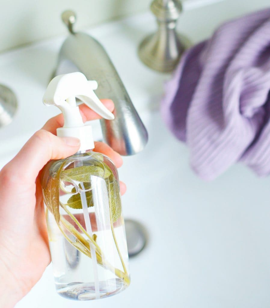 woman holding glass spray bottle filled with sage leaves for DIY spray