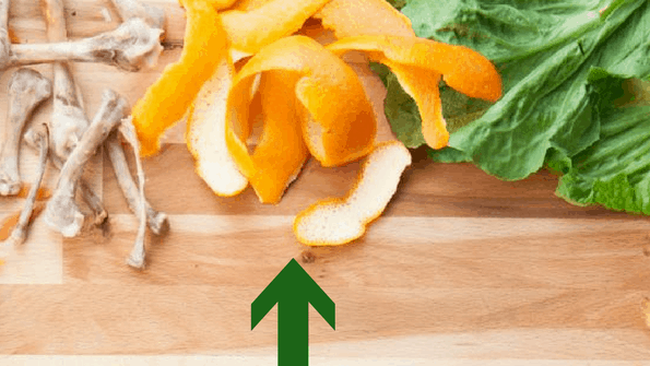 citrus peels and green leaves food waste on wood board