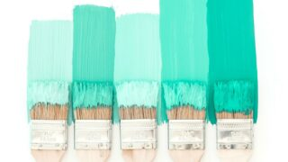 five paint brushes coated in green paint against white background