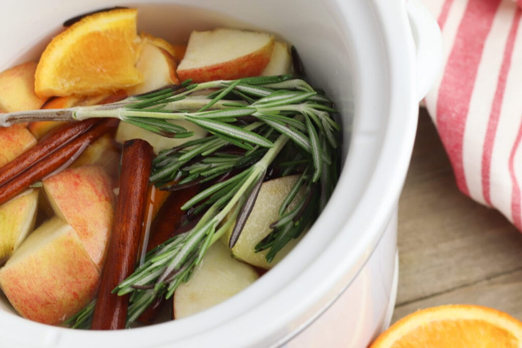 oranges apples cinnamon sticks and rosemary in a white crock pot potpourri