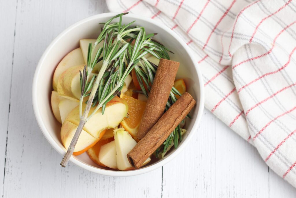 apples cinnamon sticks and rosemary in a white crock pot