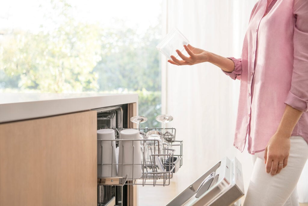 woman holding dishes by Bosch AutoAir dishwasher with door open