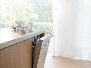 Bosch dishwasher with door open in front of window