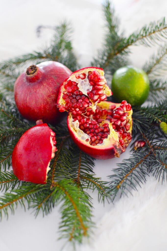 pomegranates and limes on fresh pine needles