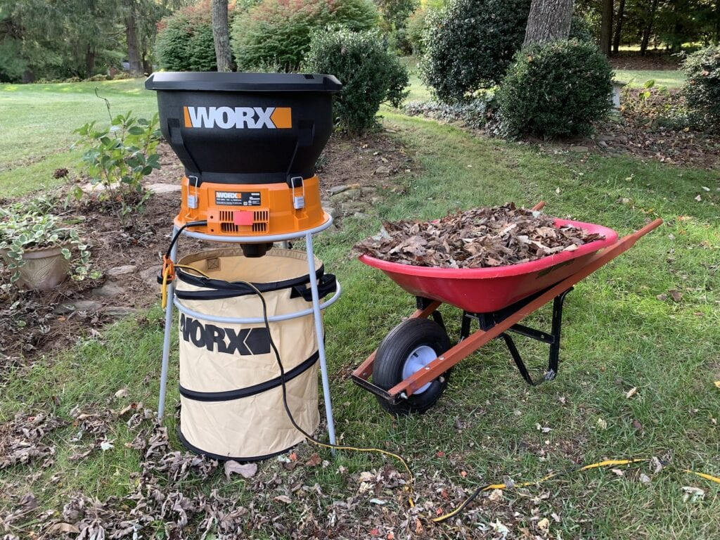 worx leaf shredder with red wheelbarrow filled with dead leaves for mulching