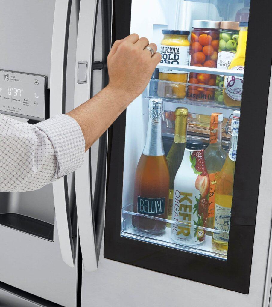 woman knocking on glass door of LG InstaView Door-in-Door Refrigerator