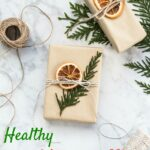 gift wrapped in brown paper with evergreen and dried orange topper