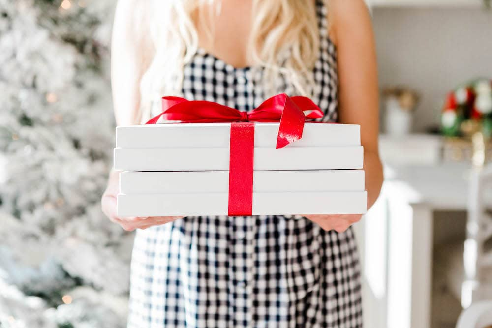 woman in dress holding white presents in front of Christmas tree