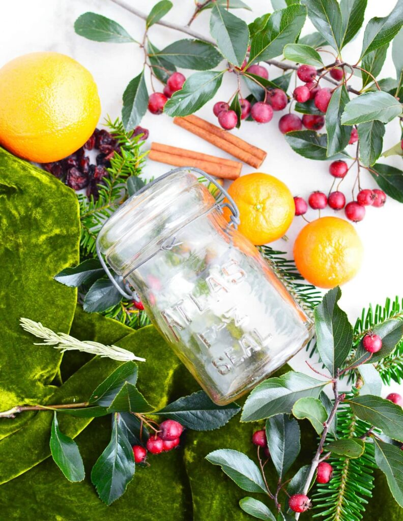glass jar on crab apple oranges and greenery