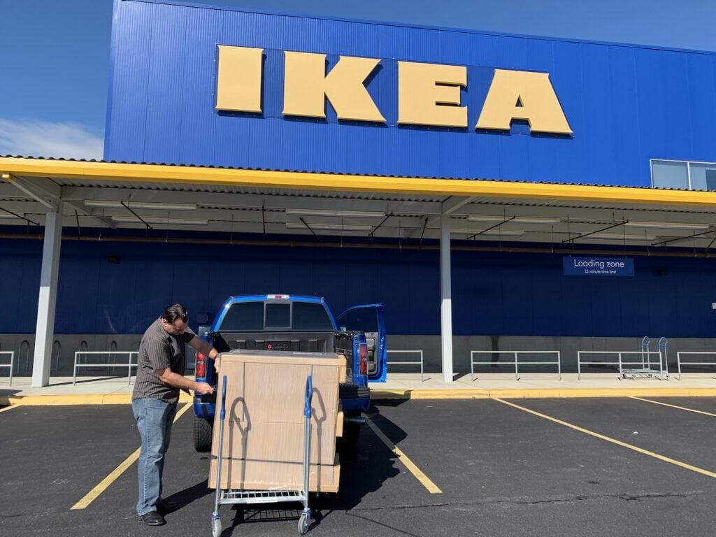 man loading IKEA furniture boxes into truck outside of IKEA store