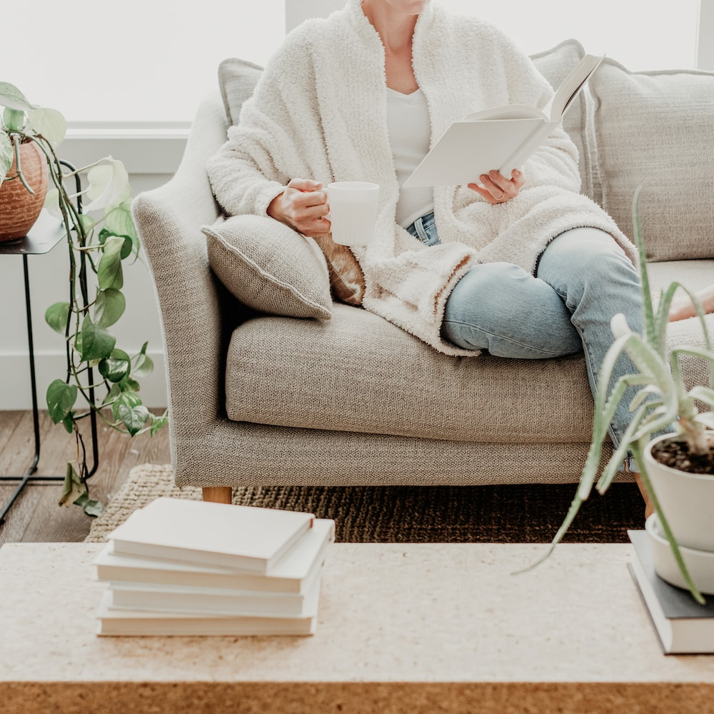 woman sitting on couch reading a book
