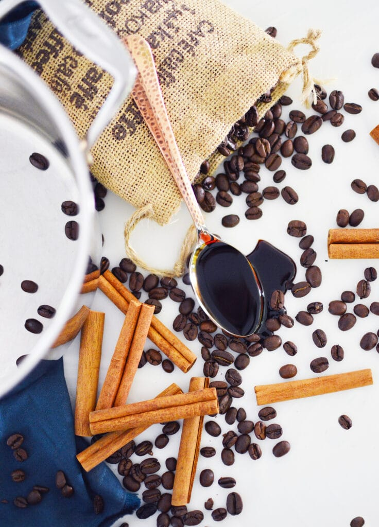 coffee beans cinnamon sticks and molasses on white background