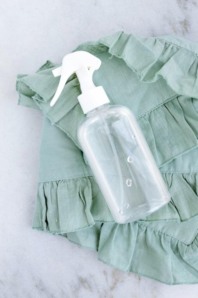 clear glass spray bottle on green towel