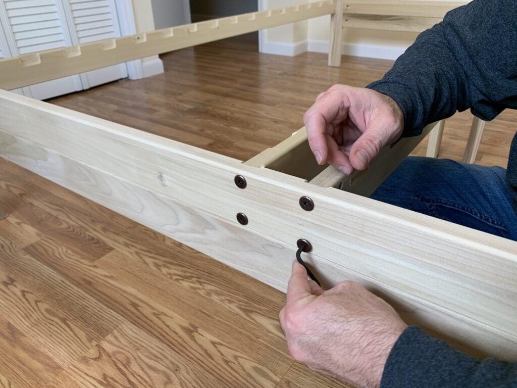 solid wood platform bed frame being put together