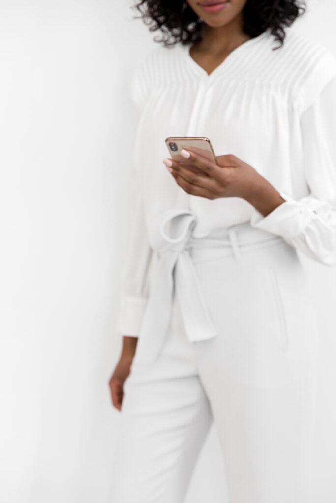 woman in white scrolling on phone on social media