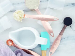 copper measuring spoons with charcoal shea butter and bentonite clay ingredients on white surface
