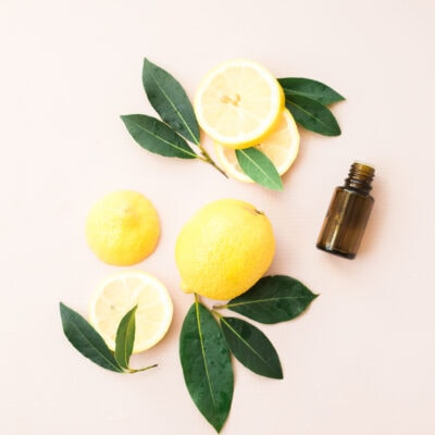 sliced lemons and leaves with brown essential oil bottle on pink background