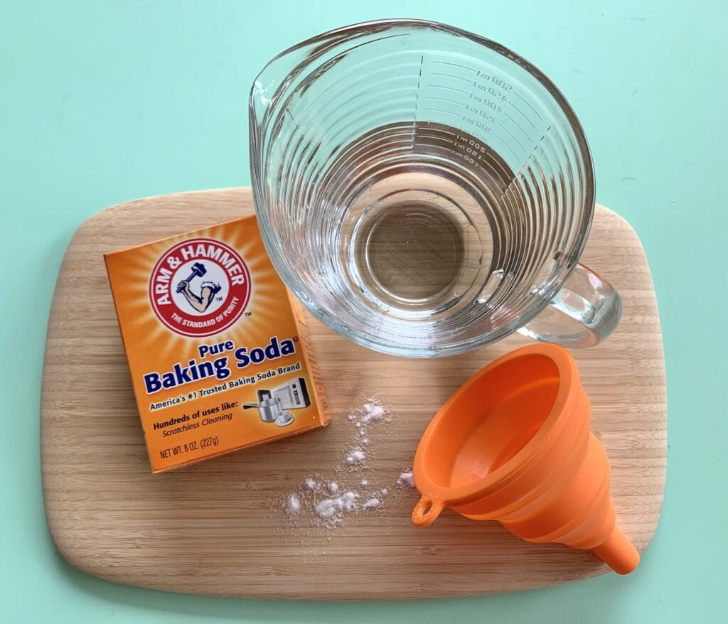 baking soda box funnel and glass measuring cup of water on wooden board against green table