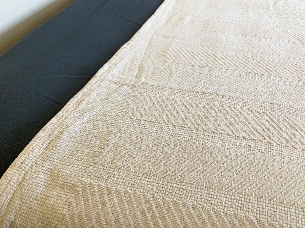 natural organic cotton blanket on bed with grey sheets