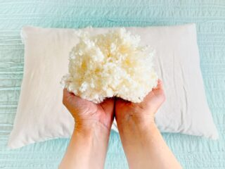 woman holding wool latex fill from customizable pillow