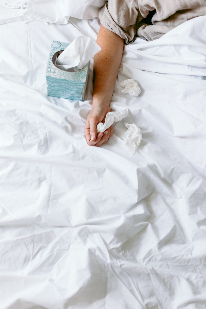 woman's hand holding bath tissues in bed with white sheets