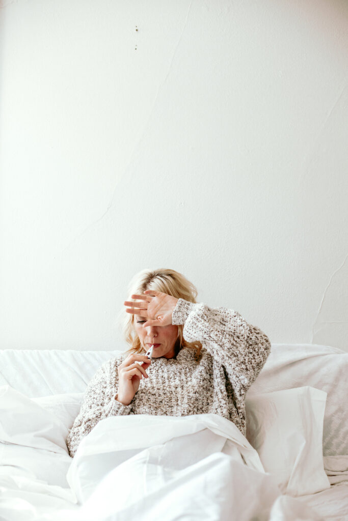 woman taking temperature in bed against white wall