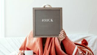 Woman holding up Board saying she is sick in Bed